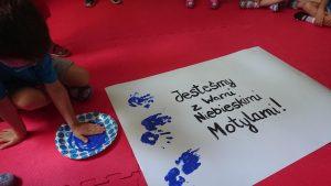 Dzieci odbijają swoje rączki zamoczone w niebieskiej farbie na białej kartce z napisem Jesteśmy z Wami niebieskimi motylami!